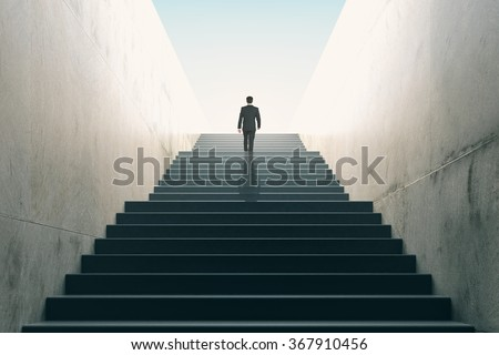 Ambitions concept with businessman climbing stairs  - stock photo