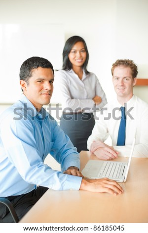 Ambitious, confident Latino man, sitting at conference room table, smiling, leading diverse business meeting with two colleagues, a minority Asian female and Caucasian male looking at camera. Vertical