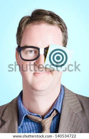Ambitious nerd businessman wearing paper note with bullseye target on face. Aims and goals - stock photo