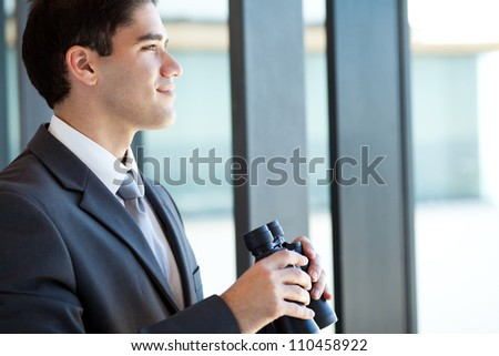 ambitious young businessman with binoculars - stock photo