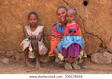 AMBOSELI, KENYA - AUGUST 31, 2013: Unidentified Masai woman and her children with traditional decorations and colorful red garments in a rural village.