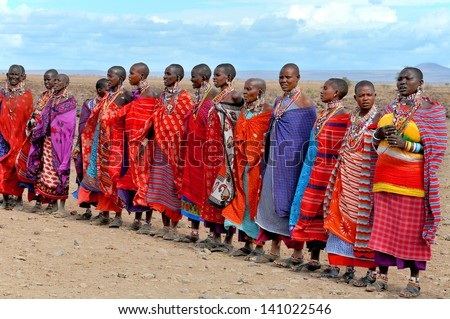 AMBOSELI, KENYA - OCT 13: Group of unidentified African people from Masai tribe prepare to show a traditional Jump dance on Oct 13, 2011 in Amboseli, Kenya. They are nomadic and live in small villages - stock photo