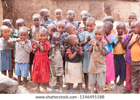 Amboseli National Park, Kenya - September, 2014: Maasai kids surrounded with flies near school posing for photographer, laughing and demonstrating how they can count. Selective focus