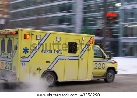 Ambulance car speeding blurred motion in american city on street warning lights flashing dramatic smoke - stock photo
