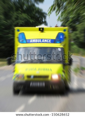 Ambulance in road with zoom effect focusing on sign.