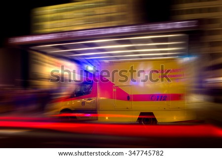 Ambulance on Emergency speedy through nightly traffic in Berlin, Germany.Motion Blur. The Sign saying in German Army First Aid Emergency. - stock photo