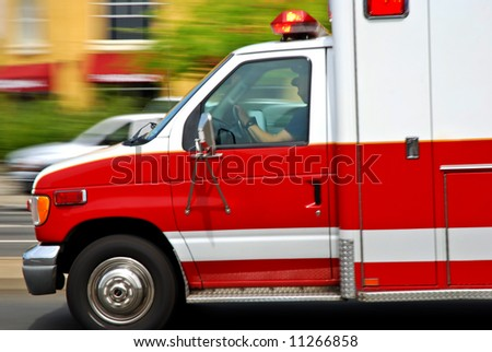 Ambulance speeding down the wrong side of an American street heading to an emergency, motion blur - stock photo