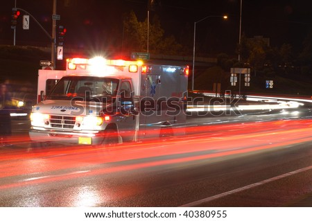 Ambulance standing in night traffic at a motor vehicle accident in early winter, Roseburg Oregon - stock photo
