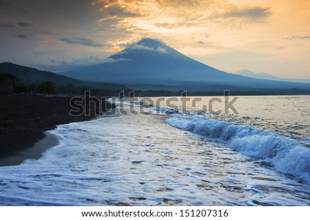 Amed, Bali, Indonesia. The volcano Gunung Agung dominates the horizon as a wave breaks over the black sand beach of this little fishing village located on the east coast of Bali.