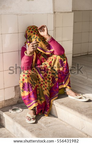 AMER, INDIA - NOVEMBER 18, 2016: An anonymous woman in a colorful sari and scarf sits against a wall at the Amber Fort in the city of Amer near Jaipur, India.