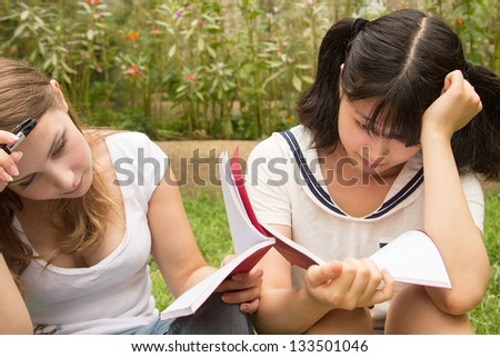 American and Asian students do homework outdoor of college. Women reading book in park. - stock photo