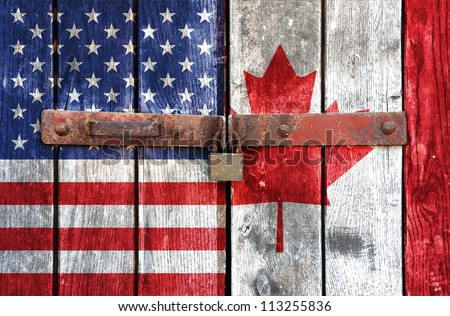 American and Canadian flag on the background of old locked doors - stock photo
