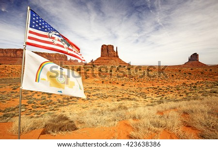 american and navajo flags waving in monument valley - stock photo