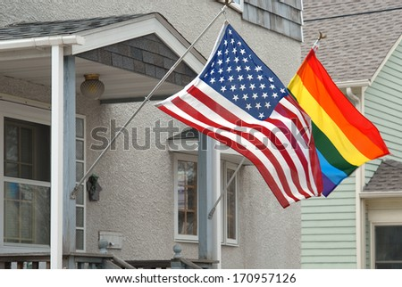 American and rainbow flag blowing in the wind on a suburban porch. - stock photo