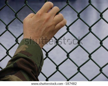 american army soldier's hand on a fence with clipping path - stock photo
