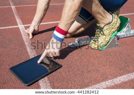 American athlete in gold running shoes crouching at the starting line of a running track wearing USA colors wristbands using his tablet