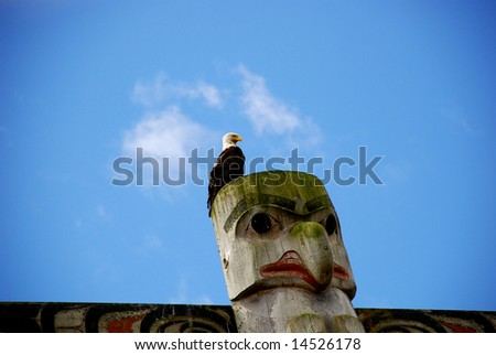 American bald eagle resting on a Native American totem pole over clear blue sky