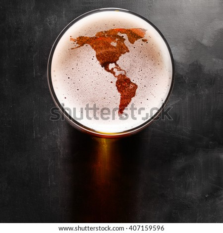 American beer concept, America silhouette on foam in beer glass on black table. The continents shapes are altered ones from visibleearth.nasa.gov - stock photo