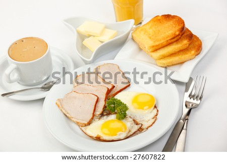 American breakfast with fried eggs, bacon, toasts, butter, juice, and coffee