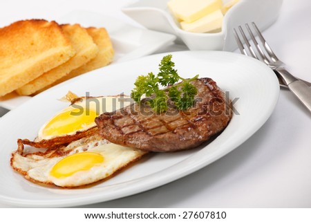 American breakfast with fried eggs, grilled meat, toasts, and butter