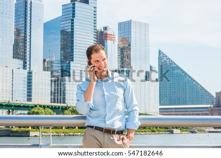 American Business Man traveling in New York in summer, wearing white shirt, stands by metal fence in busy business district with high buildings under sun, talking on cell phone.