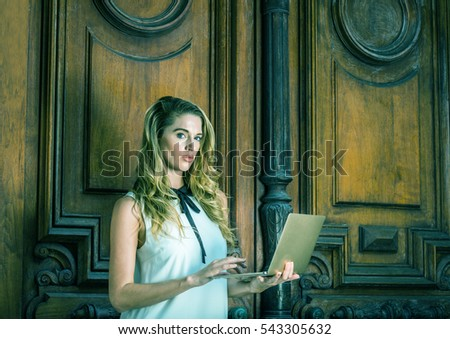 American Business Woman with long curly blonde hair working in New York, wearing sleeveless white dress, standing by vintage office door way, reading, working on laptop computer. Color filtered effect