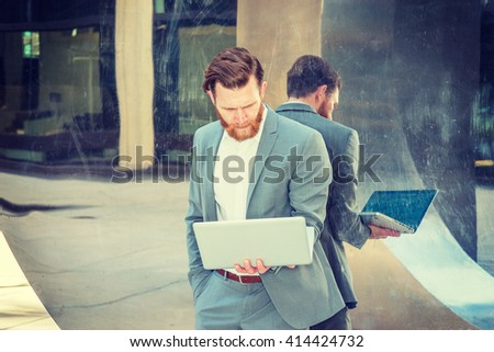 American Businessman with beard, mustache working in New York, wearing cadet blue suit, standing against metal mirror wall, looking down, reading on laptop computer. Instagram filtered effect.  - stock photo