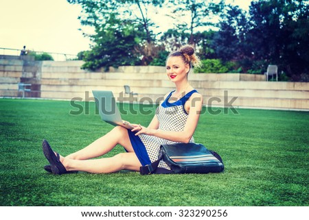 American businesswoman working in New York. A young sexy college student wearing blue, white polkadot dress, carrying leather bag, sitting on green lawn on campus, smiling, working on laptop computer. - stock photo