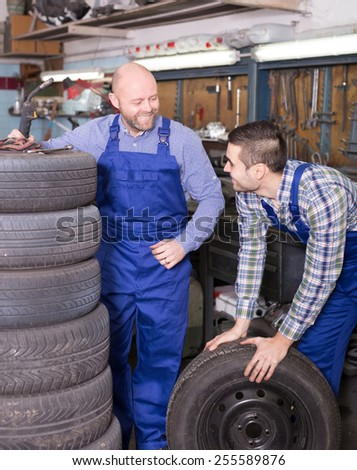 american car mechanics in coveralls working at carshop - stock photo