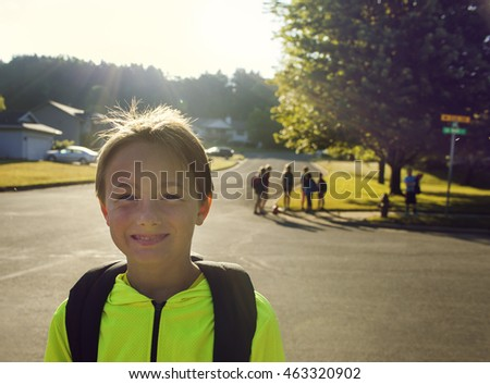 American cheerful boy waiting school bus.
