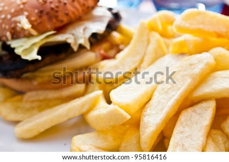 American cheese burger with golden French fries potatoes