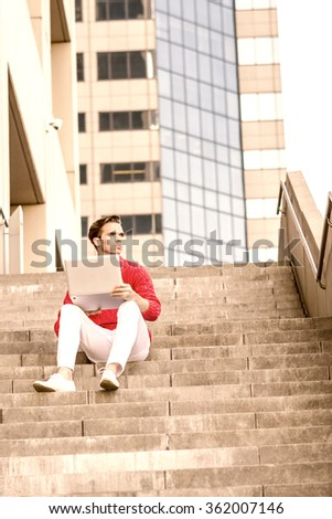 American college student reading, working on laptop computer, wearing red knit sweater, white pants, shoes, sitting on stairs outside office in New York, looking away, thinking. Color filtered effect  - stock photo