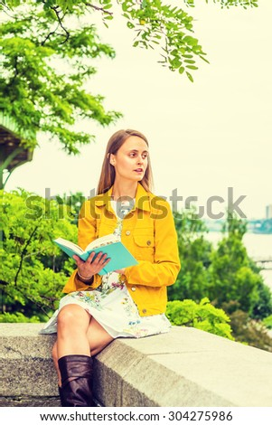 American college student studying in New York. A girl wearing flower patterned underdress, yellow corduroy jacket, holding green book, sitting by trees on campus, reading, thinking. Instagram effect.  - stock photo