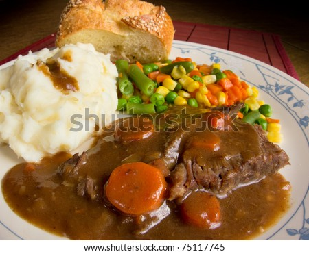 American comfort food; a heart dish of pot roast smothered in gravy, mashed potatoes and mixed vegetables.  This is a dish of real homecooked meat and potatoes. - stock photo