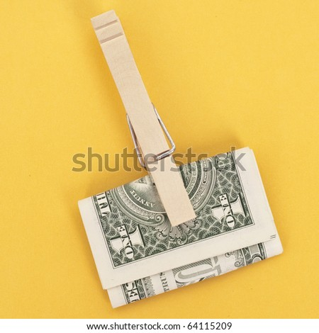 American Currency in a Clothespin on Vibrant Yellow.  Money Concept.