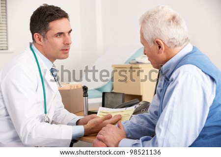 American doctor talking to senior man in surgery - stock photo