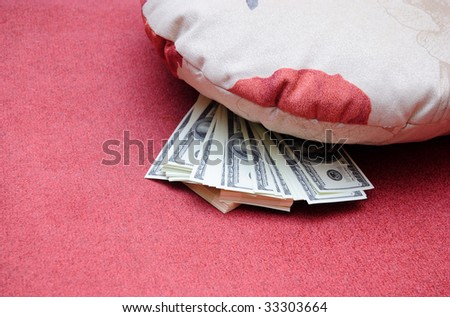 american dollars are stored under pillow - stock photo