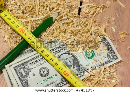 American dollars lying on the sawdust and pencil, tape-measure - stock photo