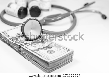 American dollars with stethoscope costs for the medical insurance with black and white color,Focus on stethoscope - stock photo