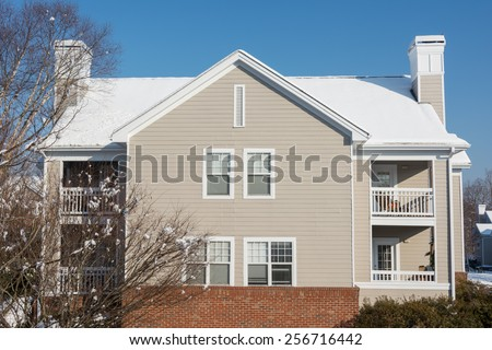 American dream house in the suburban village with snow covered the roof in winter season, located in USA - stock photo