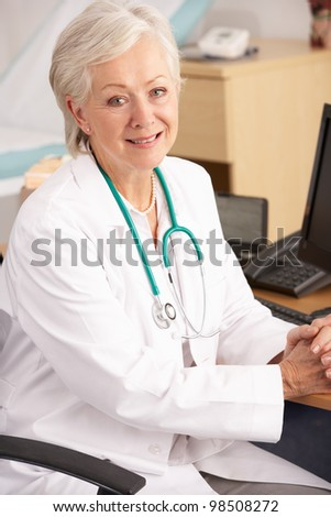 American female doctor sitting at desk - stock photo