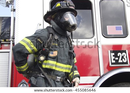 American Firefighter in a helmet and mask is near Fire Truck. (San Jose, California, United States - September 17, 2015.)