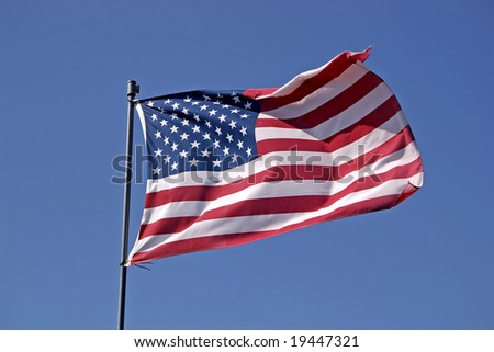 American flag against blue sky. See more flag images in my portfolio. - stock photo