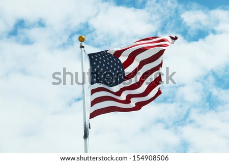American flag against bright sky with clouds - stock photo