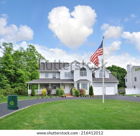 American Flag and heart shaped clouds over Suburban Mcmansion style home with recycle trash can in driveway in residential neighborhood Blue Sky Clouds USA - stock photo