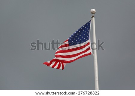 American flag back lit by direct sun with grey skies behind for dramatic vibrant colors