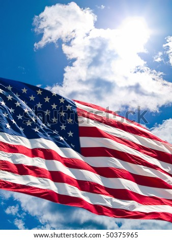American Flag Before a Cloudy Blue Sky - stock photo
