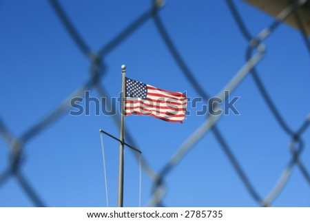 American flag behind a chain link fence. - stock photo