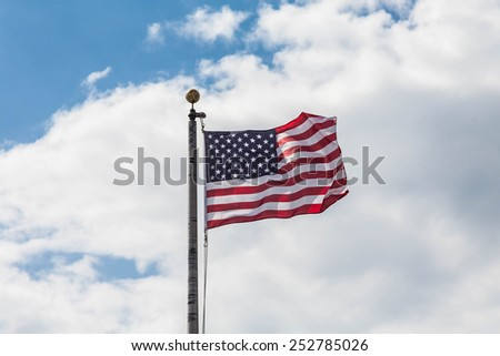 American Flag blowing in the wind at the top of a flagpole