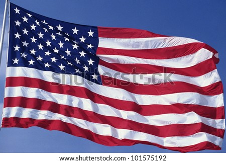 American flag blowing in the wind with a blue sky - stock photo